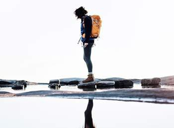 A hiker looking into a body of water, thier reflection showing under them.