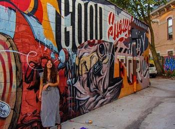 Girl in a long dress standing in front of a boldly colored mural