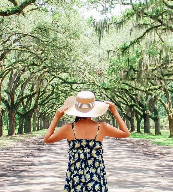 Girl with large straw sun hat look up a tree lined road