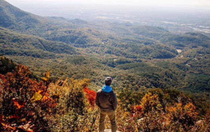 A hiker overlooking a valley of colorful trees in autumn.